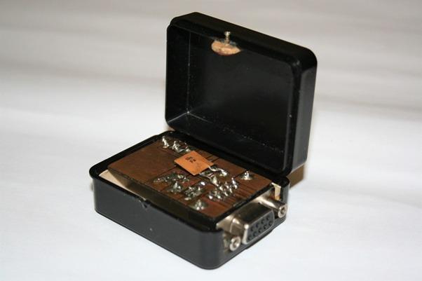 Otvorená krabička (55 x 40 x 25) s kľúčovacím obvodom, konektorom RS232 a jackom. Pohľad zo strany spojov. Prepojenia boli vytvorené technikou vyškrabovania medenej vrstvy.